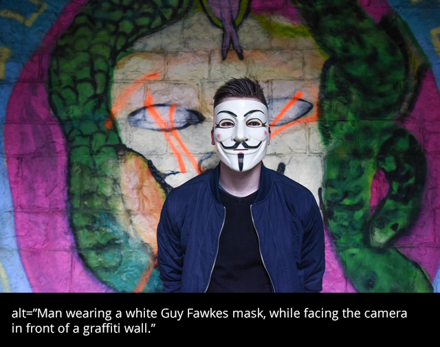 """Man with a white Guy Fawkes mask is facing camera in front of a graffiti wall."